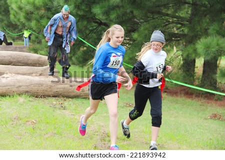 MUSKOGEE, OK - Sept. 13: Athletes overcome obstacles and try to avoid bloody zombies during the Castle Zombie Run at the Castle of Muskogee in Muskogee, OK on September 13, 2014. - stock photo