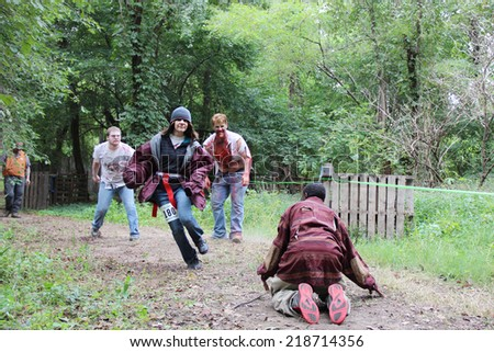 MUSKOGEE, OK - Sept. 13: Athletes try to avoid bloody zombies during the Castle Zombie Run at the Castle of Muskogee in Muskogee, OK on September 13, 2014.  - stock photo