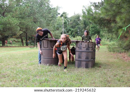 MUSKOGEE, OK - Sept. 13: Athletes try to run through obstacles and avoid bloody zombies during the Castle Zombie Run at the Castle of Muskogee in Muskogee, OK on September 13, 2014.