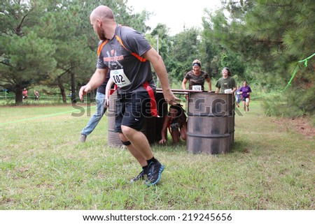 MUSKOGEE, OK - Sept. 13: Athletes try to run through obstacles and avoid bloody zombies during the Castle Zombie Run at the Castle of Muskogee in Muskogee, OK on September 13, 2014.  - stock photo