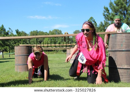 MUSKOGEE, OK - Sept. 12: Runners try to avoid bloody zombies while going through an obstacle course during the Castle Zombie Run at the Castle of Muskogee in Muskogee, OK on September 12, 2015.   - stock photo