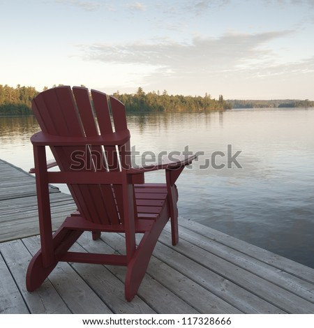 Muskoka chair on dock at Lake of the Woods, Ontario - stock photo