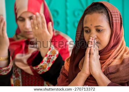 Muslim and Christian women praying together - stock photo