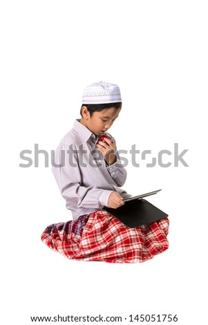 Muslim boy eating apple and play tablet. - stock photo