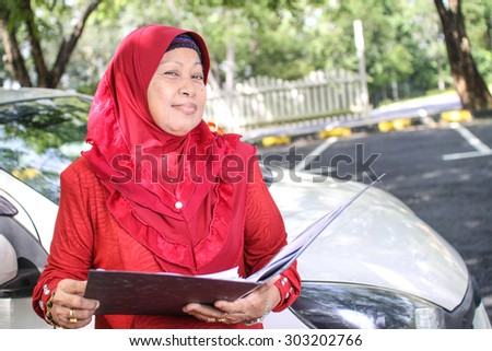 muslim business woman smiling while holding her file - stock photo