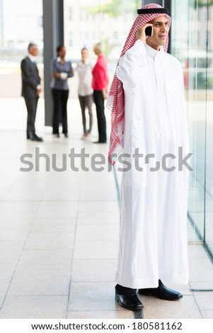 muslim businessman in traditional clothes talking on cell phone - stock photo
