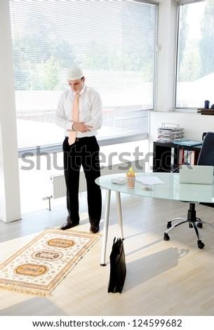 Muslim businessman praying at office - stock photo
