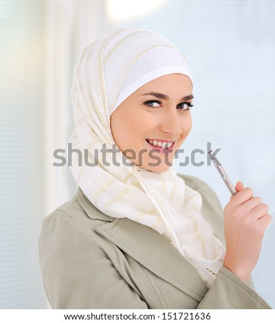 Muslim Caucasian female student holding pen - stock photo