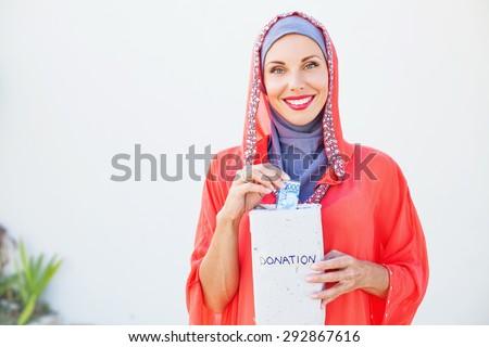 muslim caucasian woman giving alms - stock photo