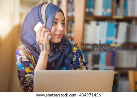 Muslim female worker talking on the phone while working with laptop computer - stock photo