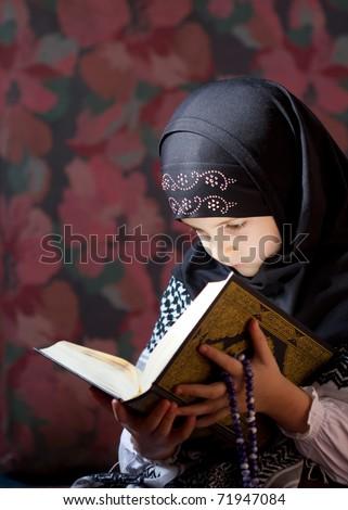 Muslim girl reading Koran - stock photo