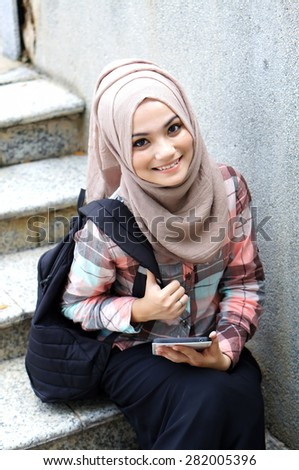 muslim girl student with her tablet sitting on the stair - stock photo