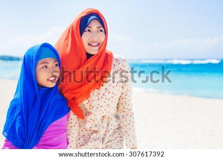 muslim girls on a beach - stock photo