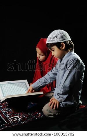 Muslim kids reading holy koran on  black background - stock photo