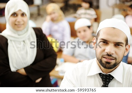 Muslim male and female teachers in classroom with childrens - stock photo