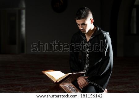 Muslim Man In Dishdasha Is Reading The Quran - stock photo