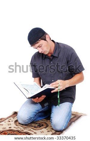 Muslim man is holding holly book Qoran and praying on traditional way - stock photo