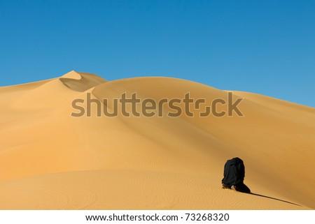 Muslim man praying in the desert - Awbari Sand Sea, Sahara Desert, Libya - stock photo
