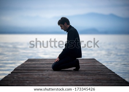 Muslim man praying on an empty dock - stock photo