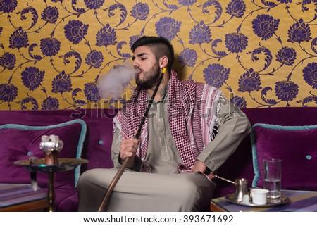 Muslim Man Smoking Shisha At Arabic Restaurant - Exhaling Smoke - stock photo