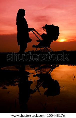 Muslim mother and baby walking during sunset with stroller.