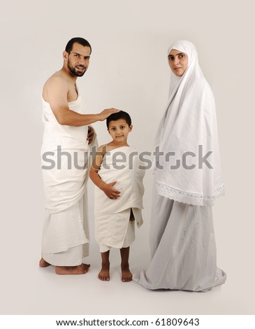 muslim pilgrims in white traditional clothes, family, woman, man and child (wife and husband and son) - stock photo