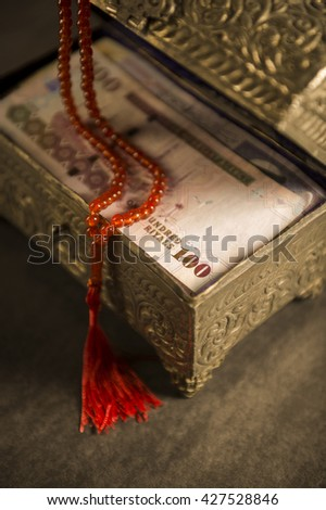 Muslim prayer beads and Saudi currency notes in vintage chest. - stock photo