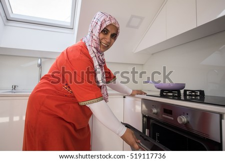 Muslim traditional woman using stove