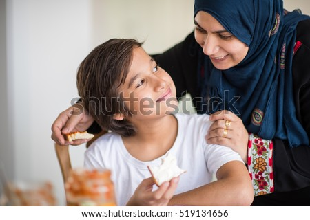 Muslim traditional woman with son at kitchen