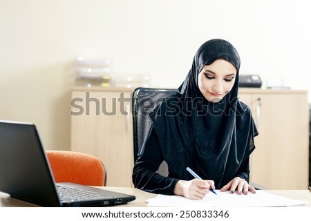 Muslim woman fills the documents while working in the office - stock photo