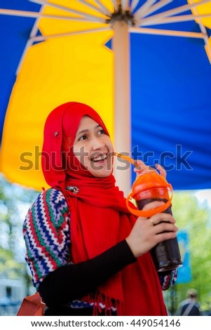 Muslim woman from Indonesia travel to an amusement park in Canada - stock photo