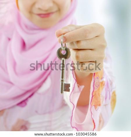 Muslim woman hand holding a new key - stock photo