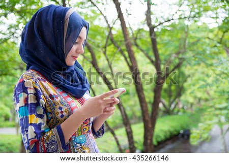 Muslim woman standing with mobile phone.