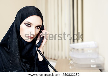 Muslim woman talking on a landline phone at the office - stock photo