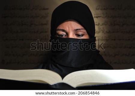 Muslim woman who studies the Koran - stock photo