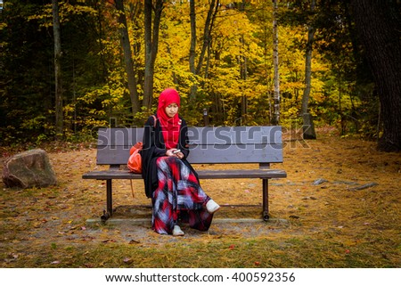 Muslim woman with colourful trees as background during autumn season