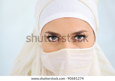 Muslim woman with veil looking at camera - stock photo