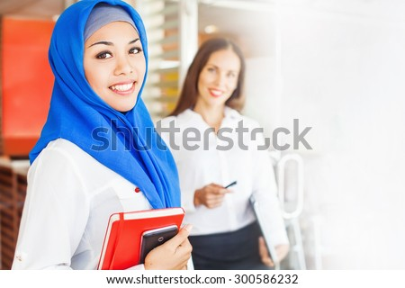 muslim woman working in office with caucasian non muslim woman - stock photo