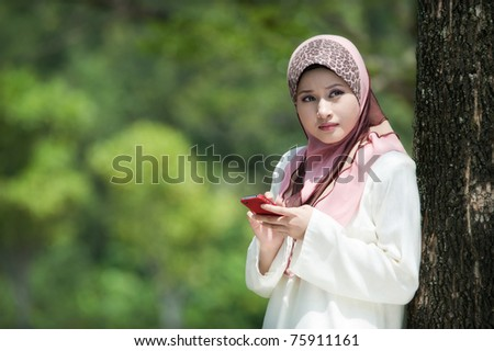 Muslim young woman in head scarf using phone in the park