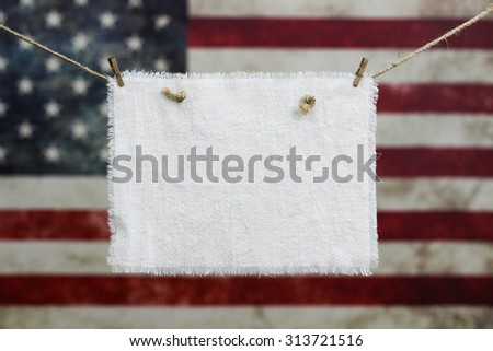 Muslin sign hanging in front of blurred background of vintage American flag on canvas - stock photo