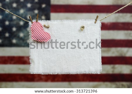 Muslin sign with red heart hanging in front of blurred background of vintage American flag on canvas - stock photo