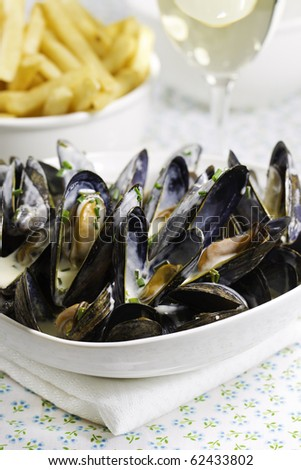 Mussel with white wine sauce and french frie  on a plate. Very shallow depth of field. - stock photo