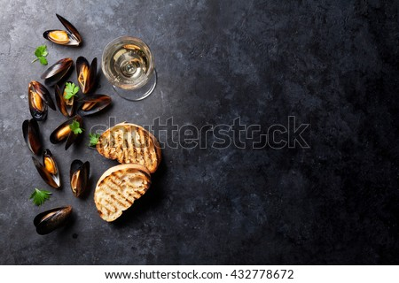 Mussels, bread toasts and white wine on stone table. View with copy space - stock photo