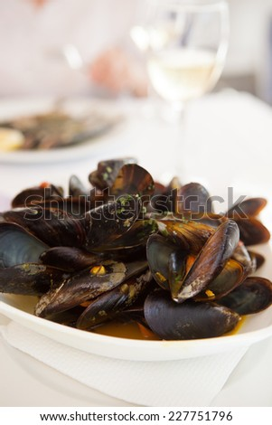 Mussels cooked in wine  with glass of wine on the background