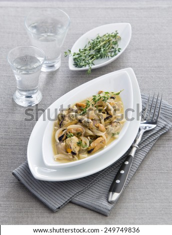 mussels in a creamy sauce with thyme on a white plate gray background - stock photo