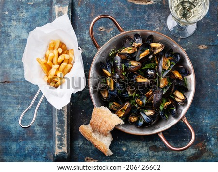 Mussels in copper cooking dish and french fries on blue background - stock photo
