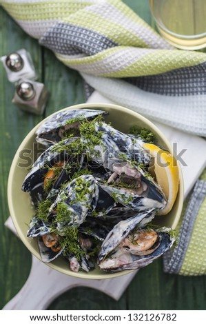 Mussels in cream and bacon on green table - stock photo