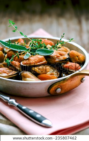 Mussels in cream and garlic sauce with provencal herbs in aluminum saucepan, shallow DOF, selective focus