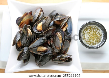 Mussels on a plate with melted butter. - stock photo