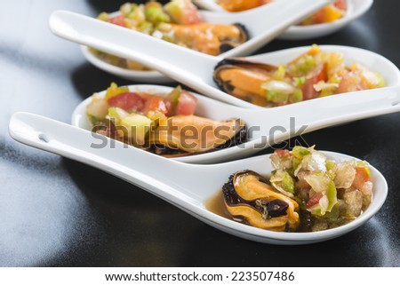 Mussels vinaigrette for a good appetizer served on chinese spoons - stock photo